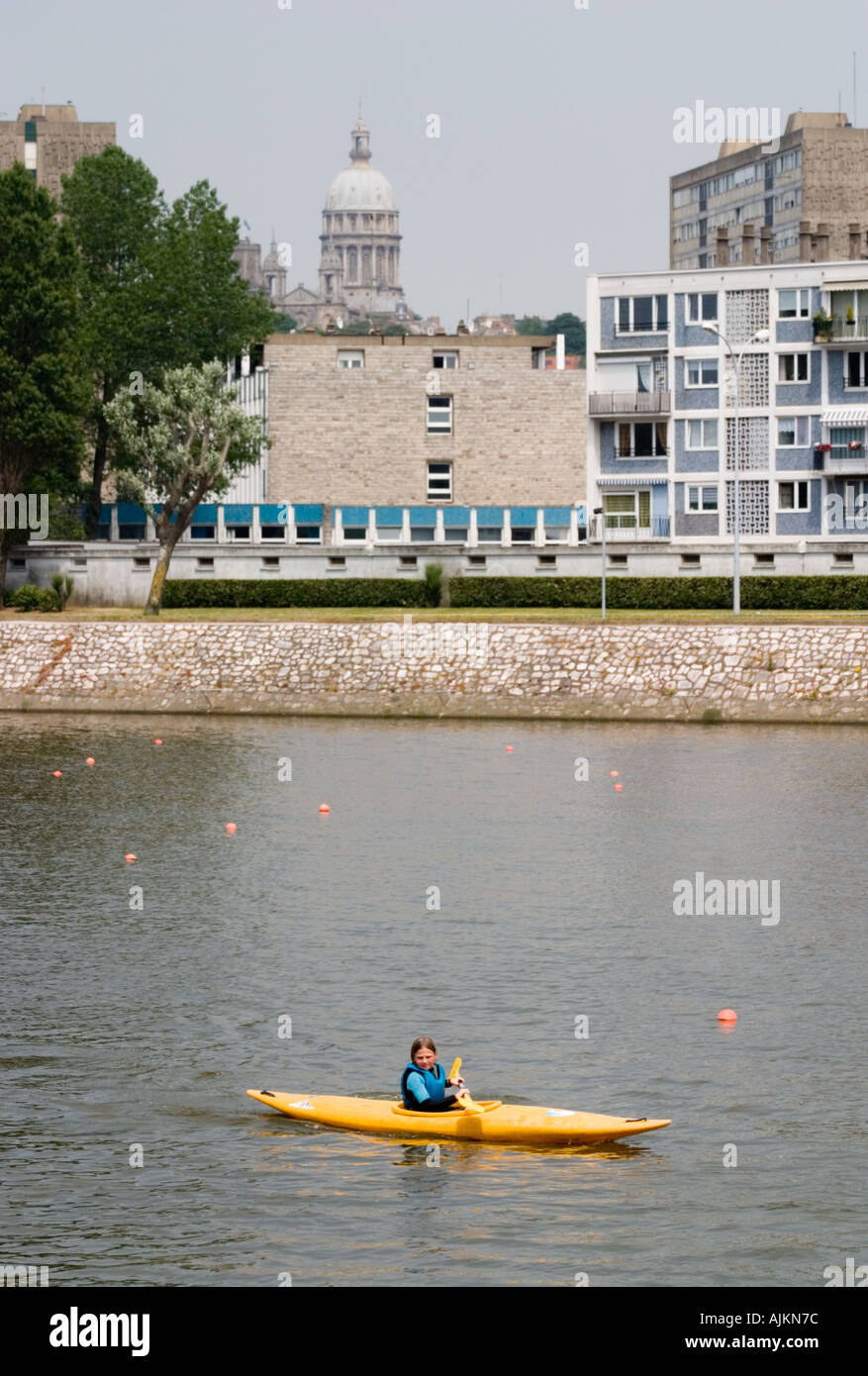 Schoolchild canoeing on river Boulogne sur Mer with cathedral dome in background - Stock Image