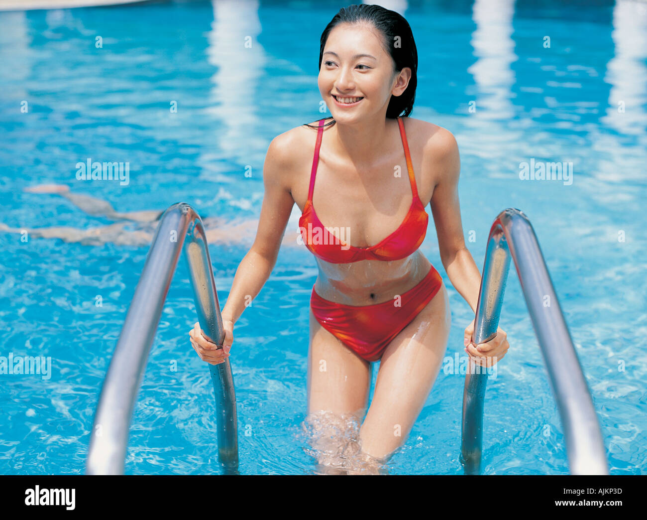 ba1bc3e57ff High angle view of a young woman stepping out of a swimming pool - Stock  Image
