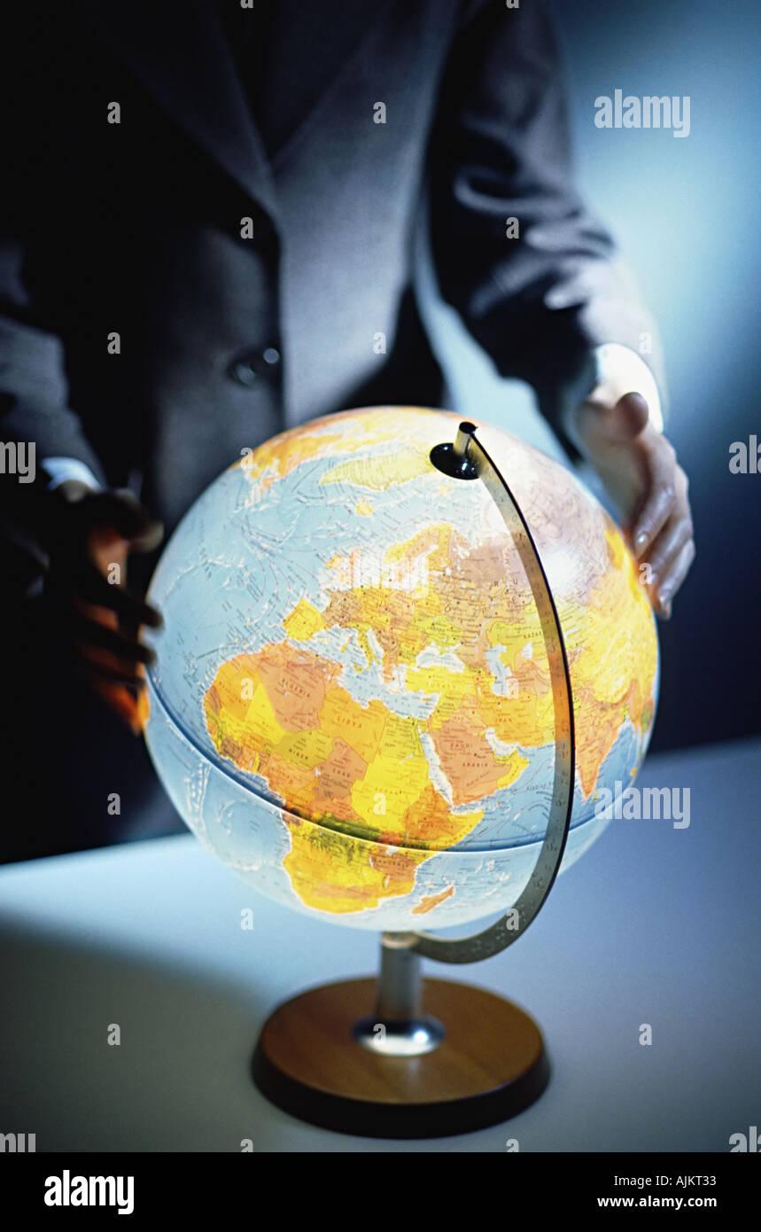 Businessman touching a globe - Stock Image