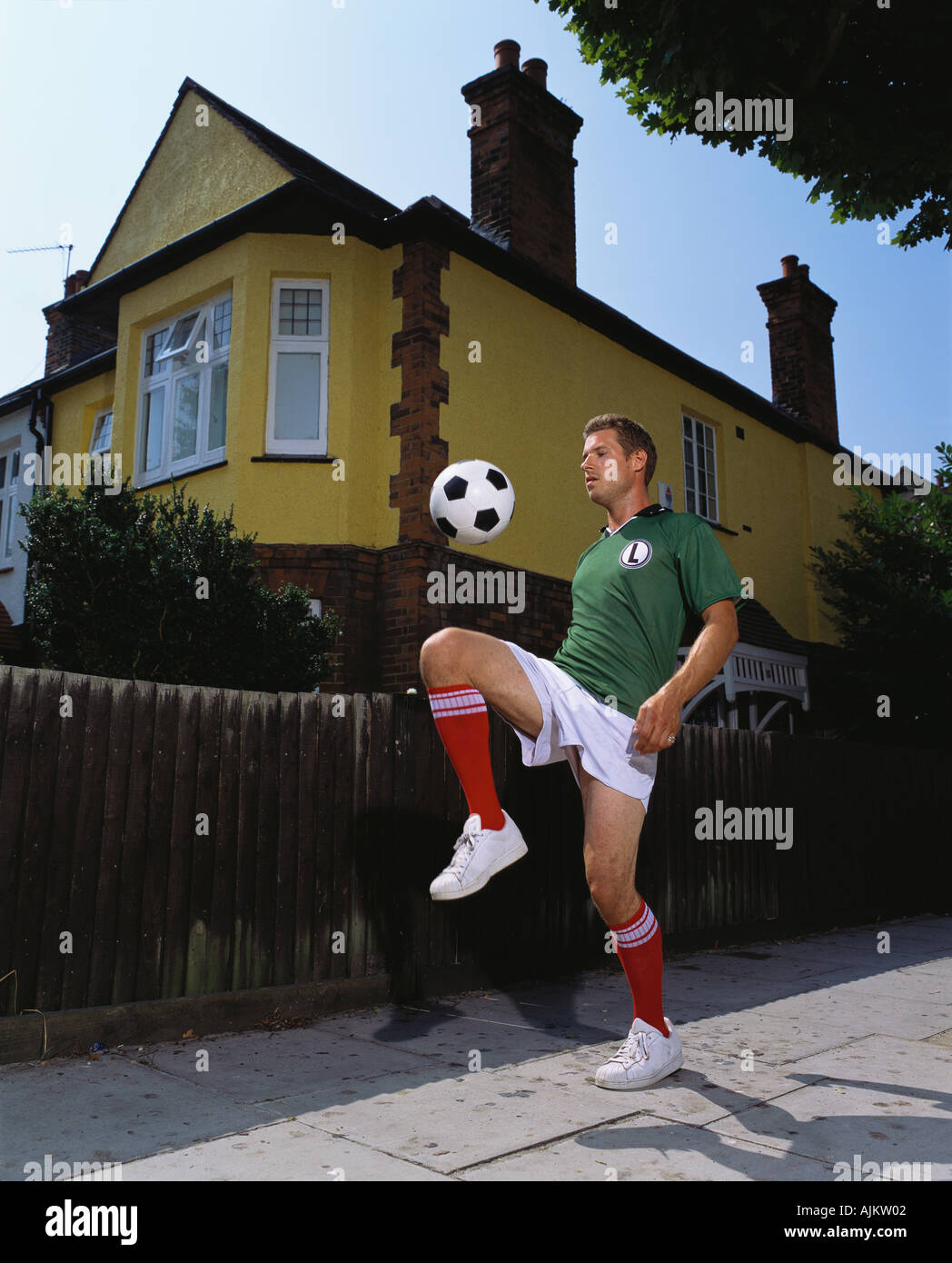 Footballer playing on pavement - Stock Image
