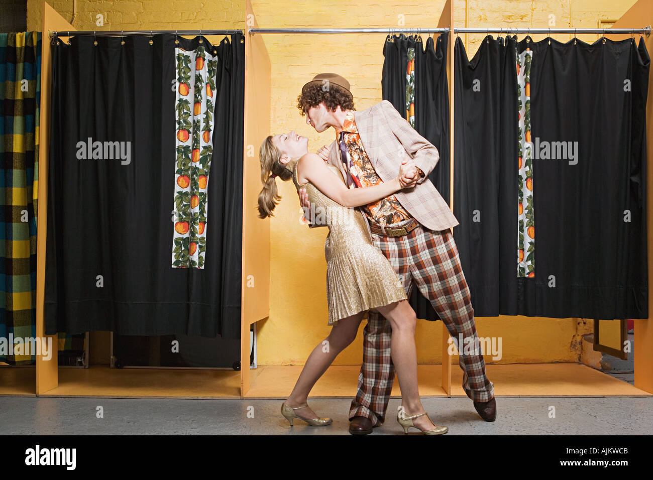Retro couple dancing in clothes store - Stock Image
