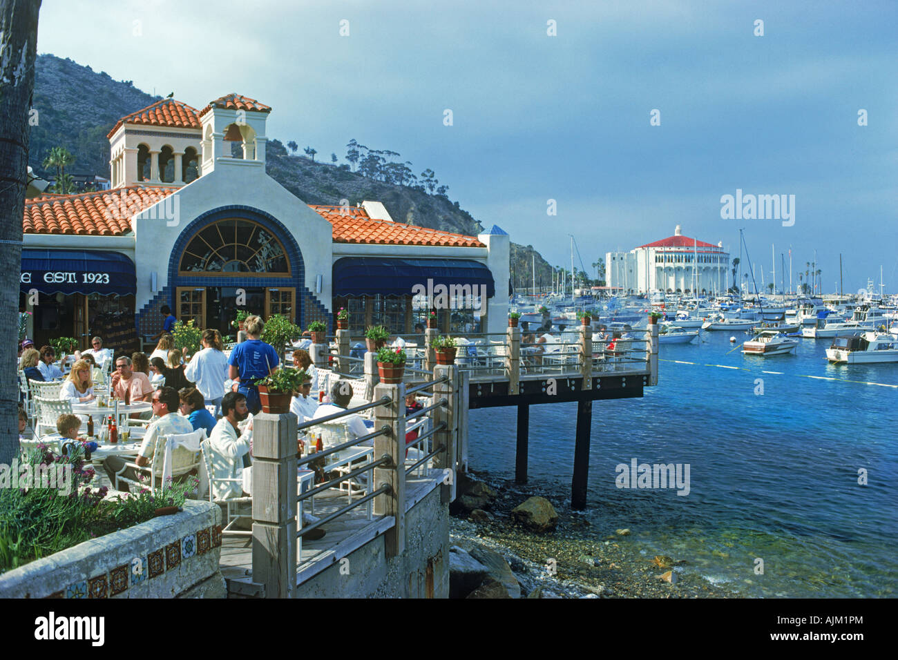 Tourists On Restaurant Balcony With Casino And Yachts At