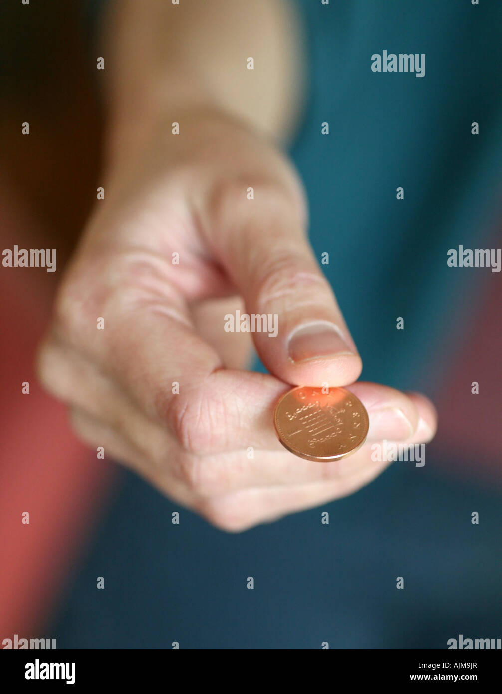 giving 1p coin - Stock Image