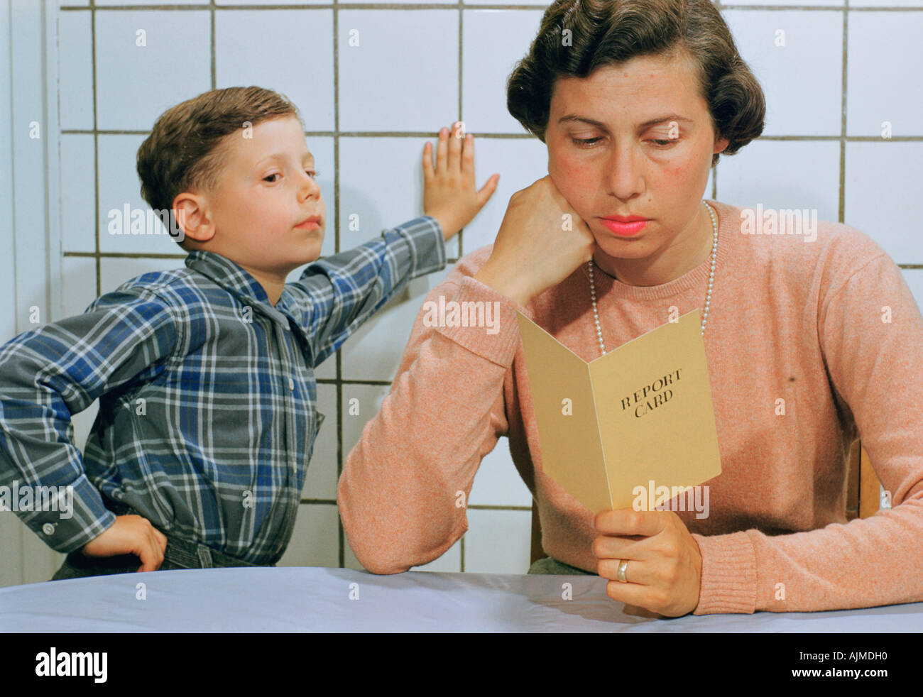 Young boy and his mother looking at his report card - Stock Image