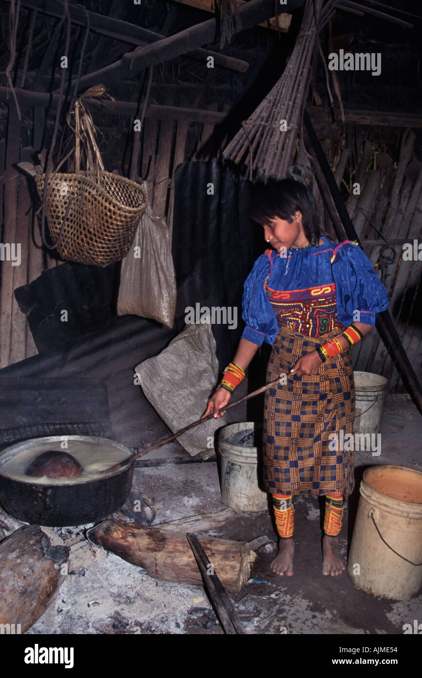 Young Kuna Indian woman preparing dinner over log fire in a soot blackened cooking hut Bayano Lake Panama Central America - Stock Image