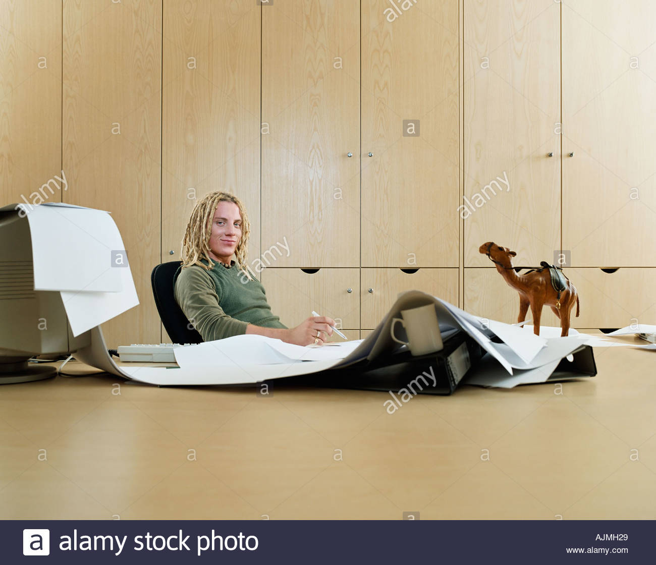 Man with messy desk - Stock Image