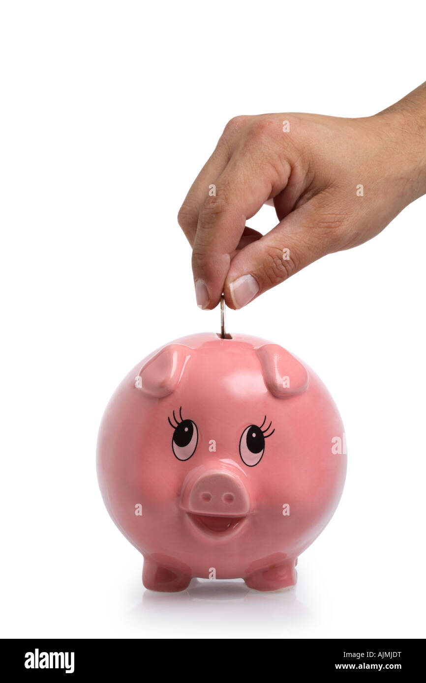 Hand putting money into piggy bank cut out on white background - Stock Image