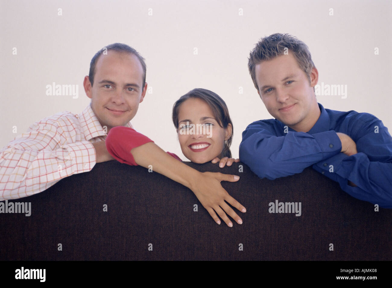 Three colleagues leaning on a divider - Stock Image