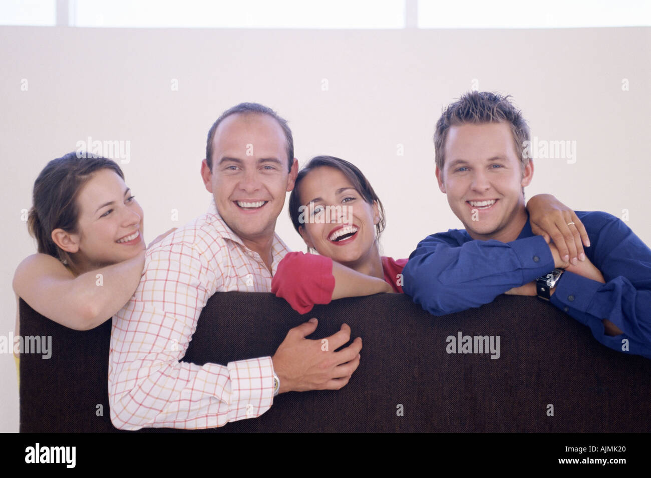 Four colleagues leaning on a divider - Stock Image