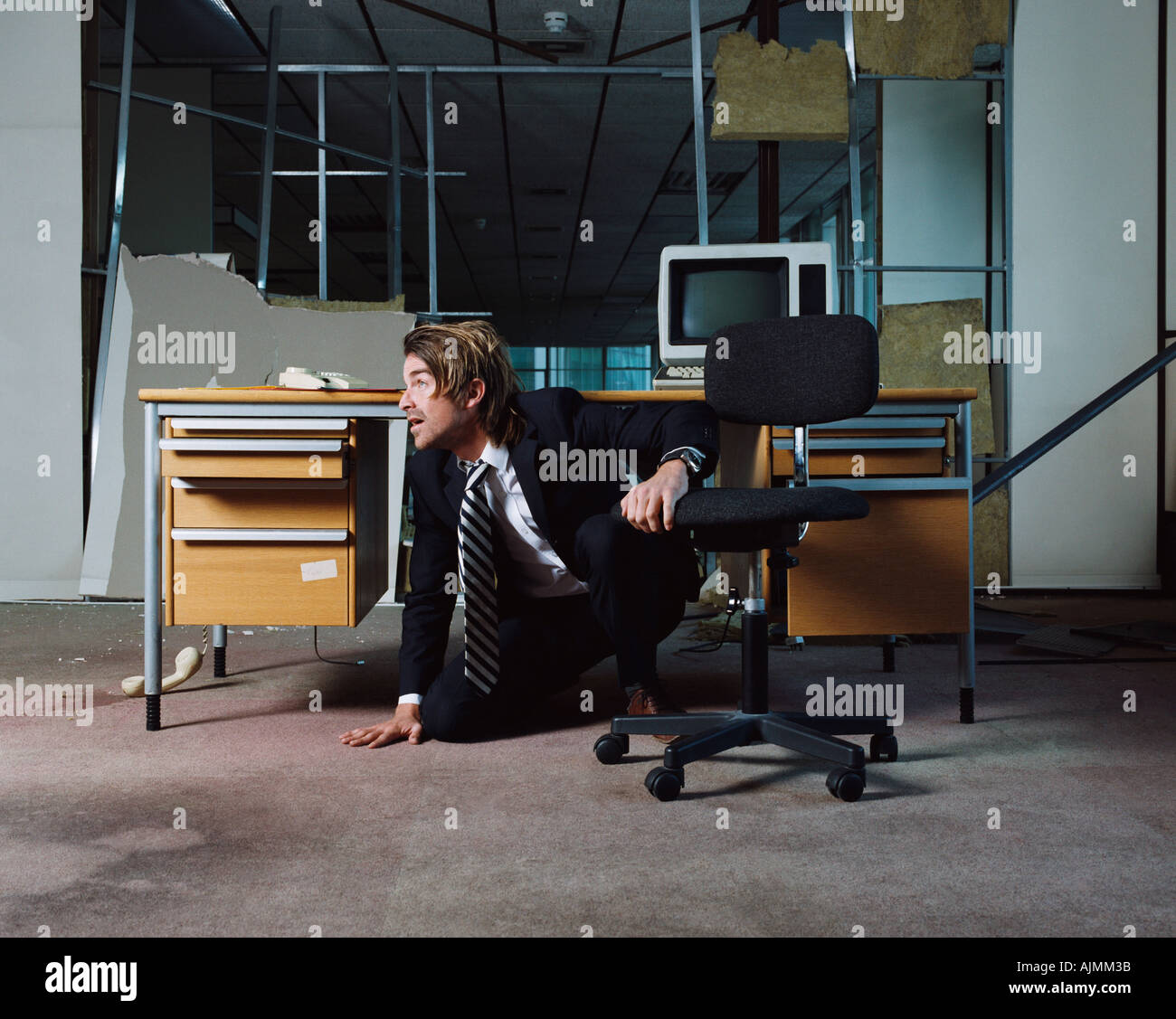 Businessman emerging from under desk - Stock Image