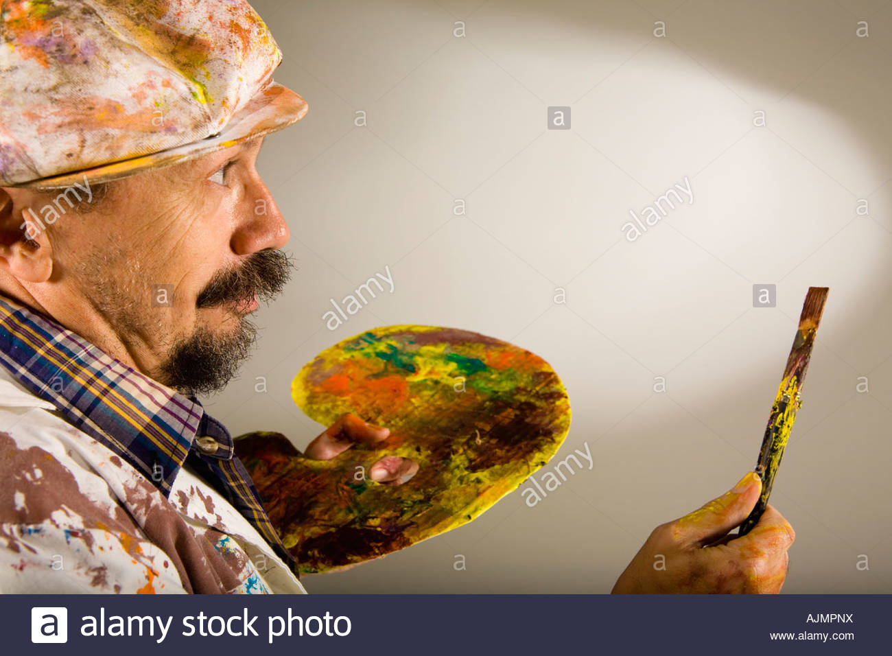 Close-up of a mature man holding a paintbrush and a palette - Stock Image