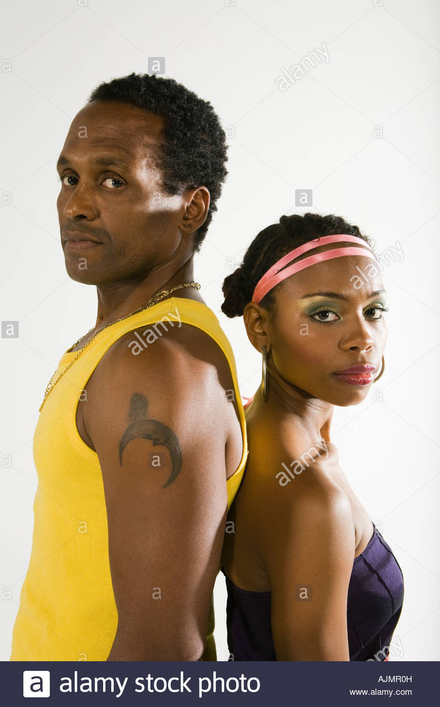 Side profile of a young couple standing back to back - Stock Image