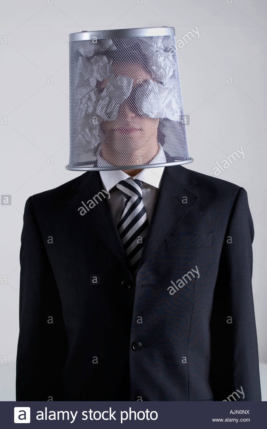 Businessman hiding his face with a wastepaper basket - Stock Image