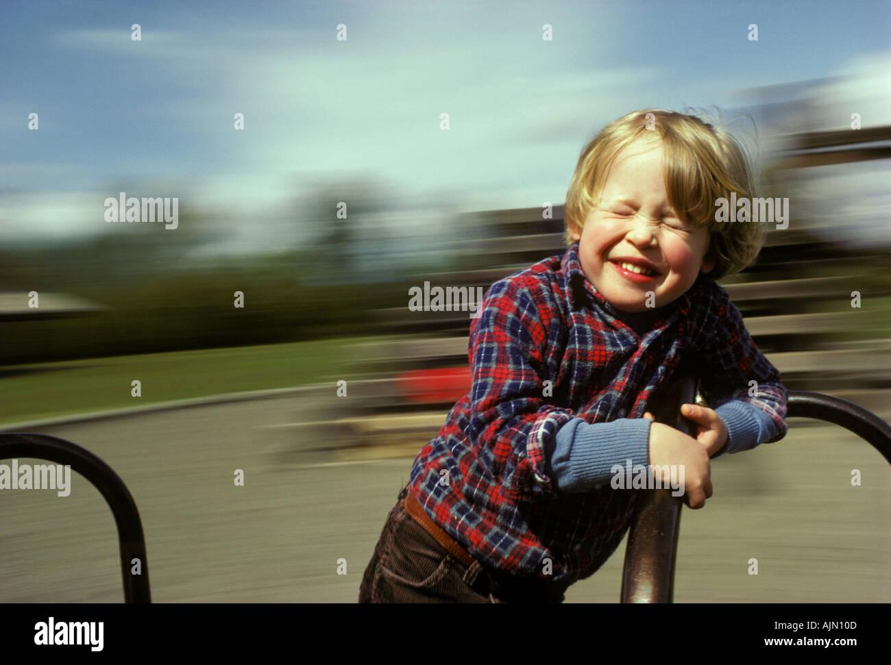 A six year old boy closes his eyes to appreciate the vertigo on a carousel - Stock Image