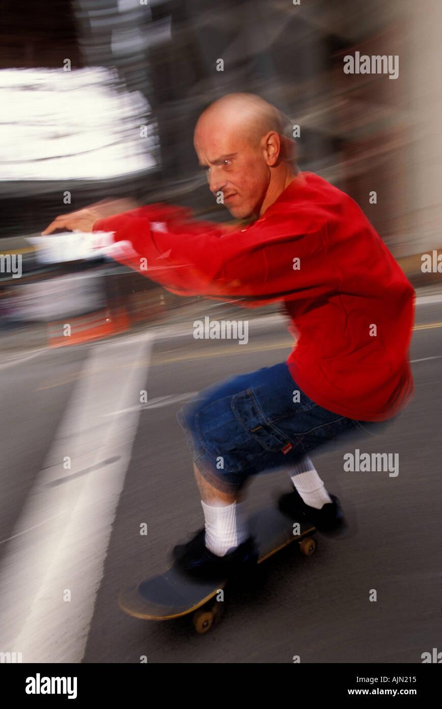 A bald skateboarder with an agressive attitude speeds along a city street - Stock Image