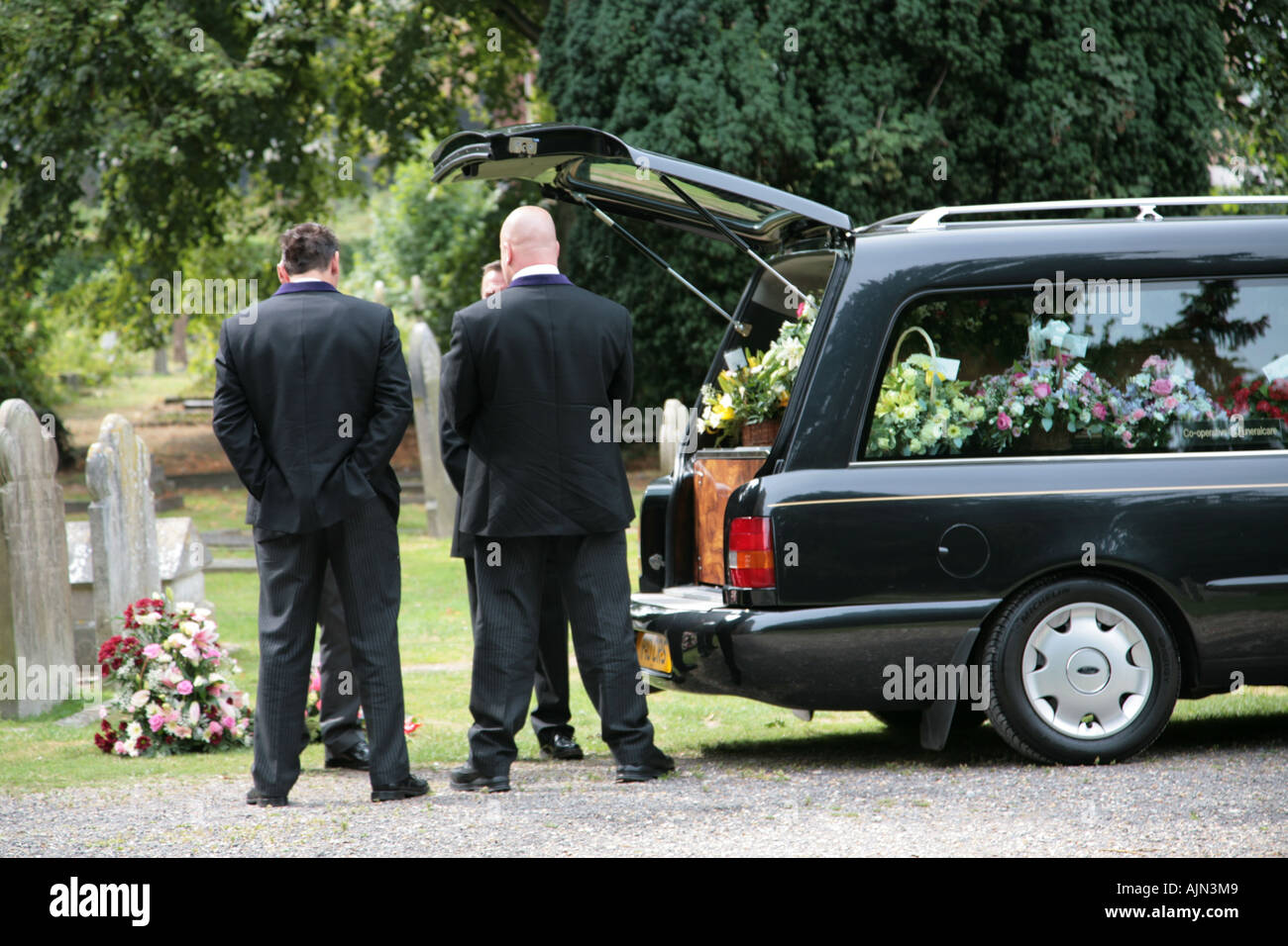 funeral directors and pall bearers preparing to remove coffin from hearse - Stock Image