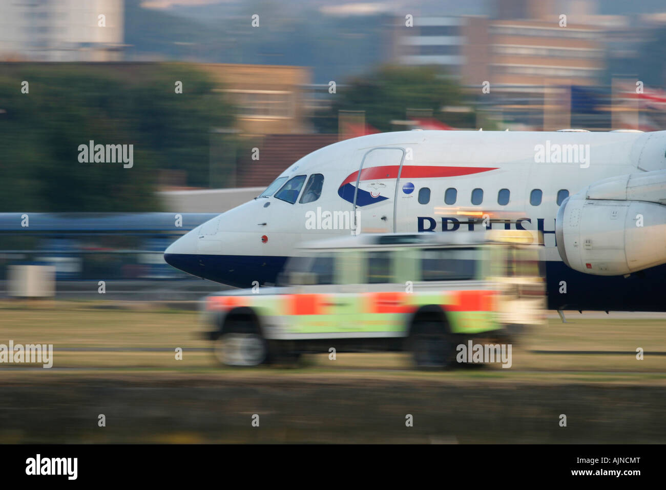 British Airways commercial jet passing behind ground crew Land Rover during take off London City Airport, England, - Stock Image