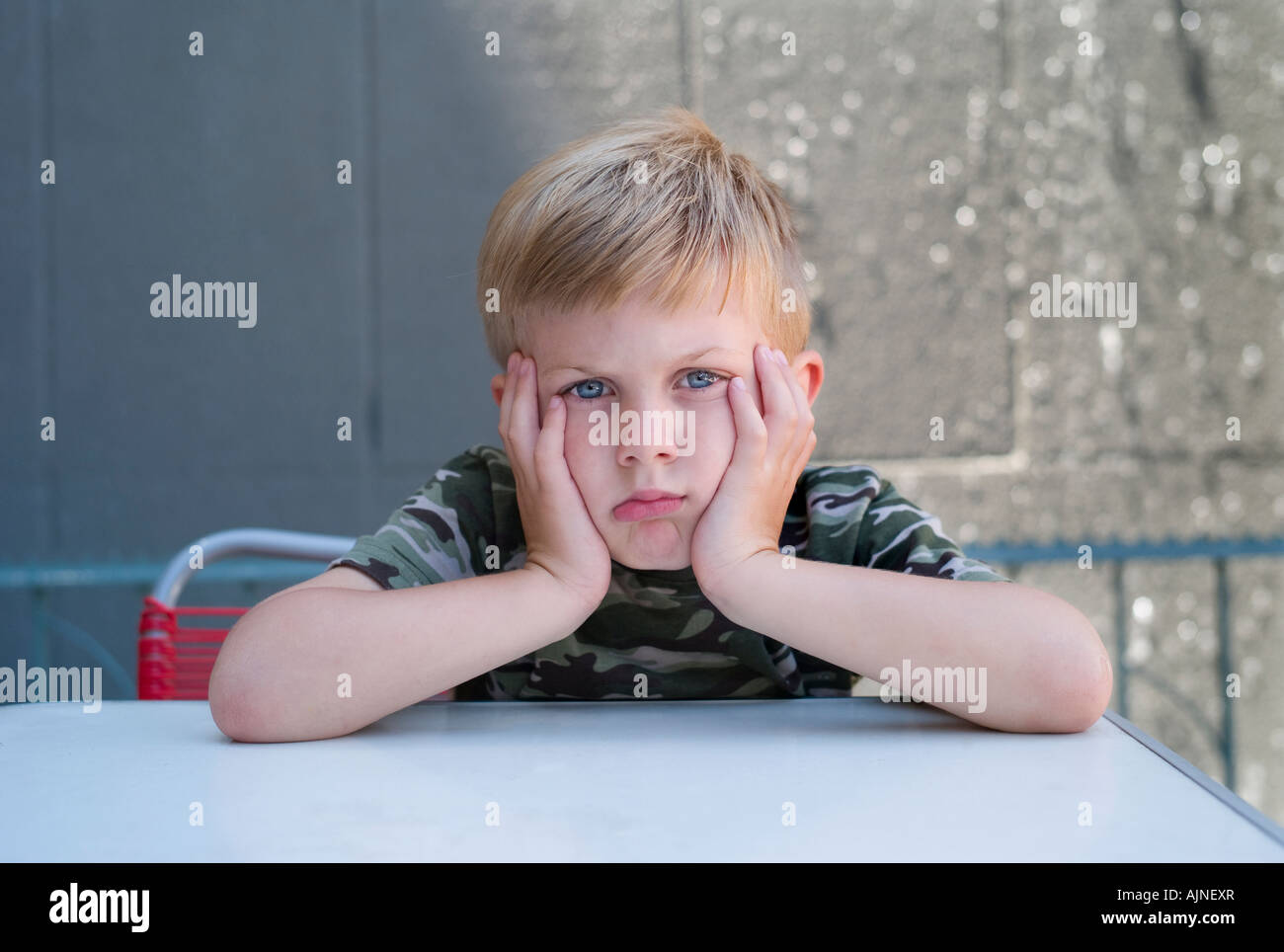 Bored or serious small boy - Stock Image