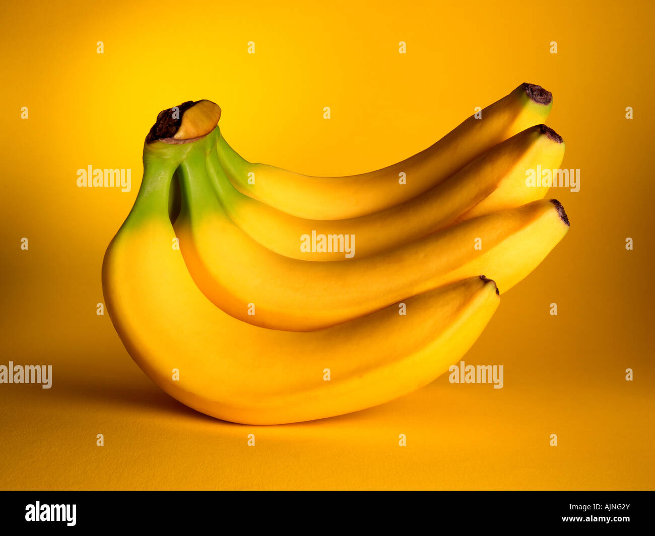 A BUNCH OF YELLOW BANANAS ON A MATCHING YELLOW BACKGROUND - Stock Image
