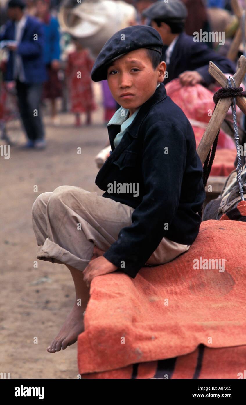 Young Uyghur boy sitting on a cart Kashgar market Kashgar is at the end of the Karakoram Highway China - Stock Image