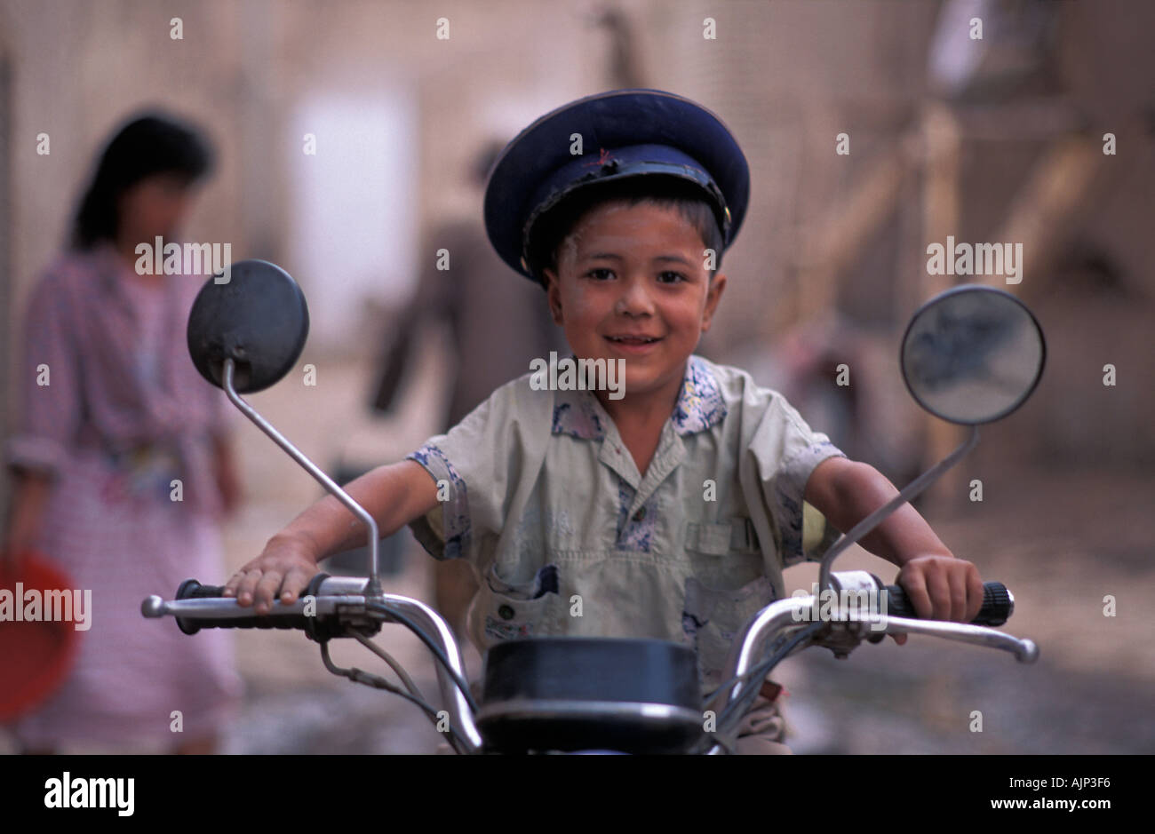 Boy seated on a motorcycle in the backstreets of Kashgar Kashgar is at the Chinese end of the Karakoram Highway China - Stock Image