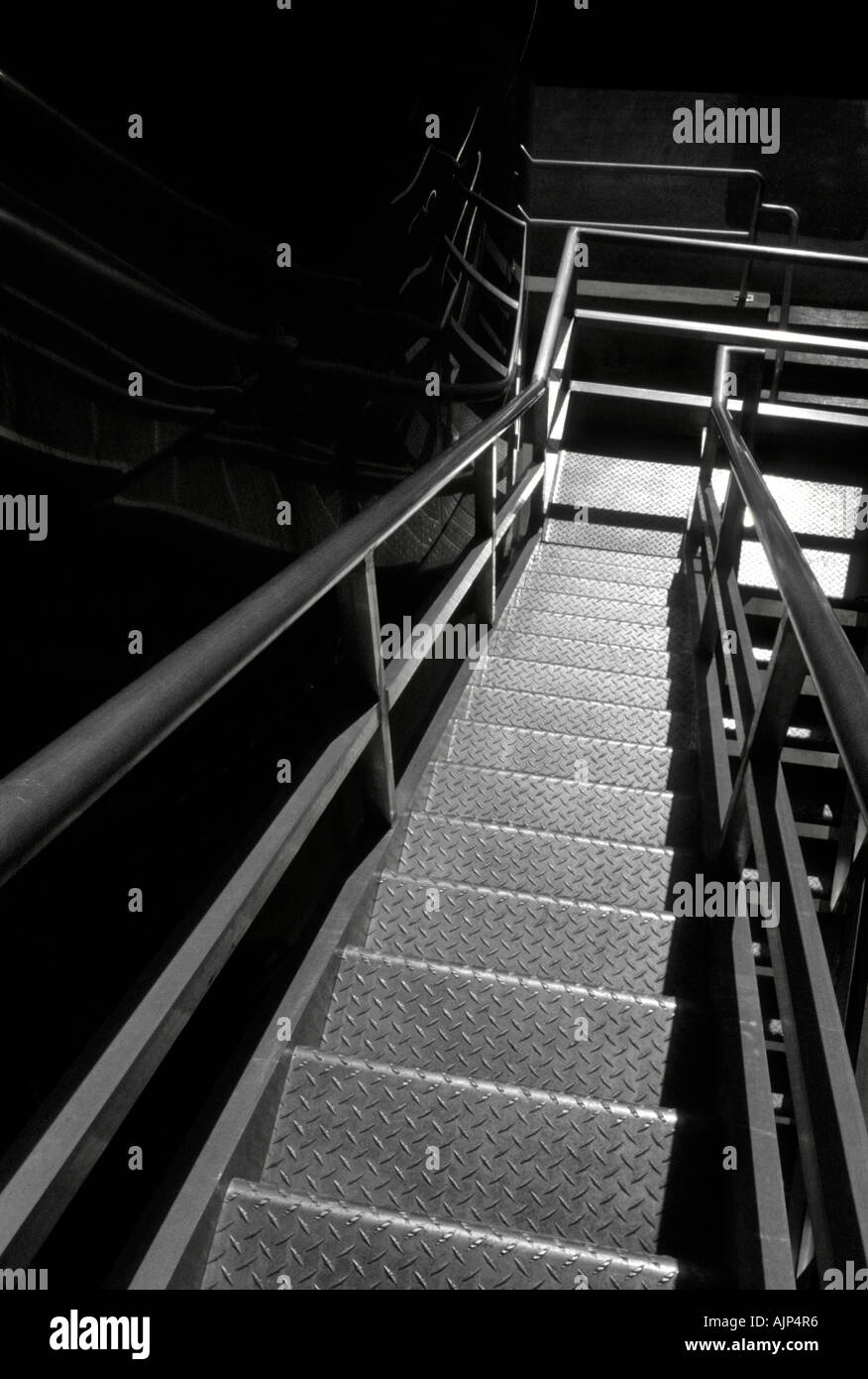 A bright lighted metal stairway leading down - Stock Image