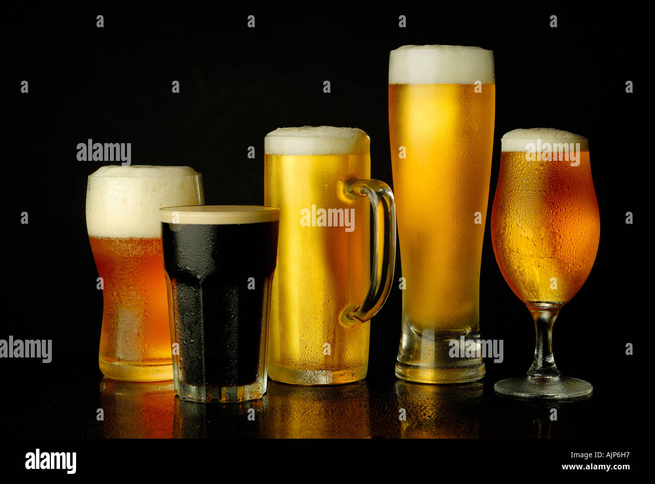 BEER COLORFUL VARIETY MUGS OF COLD BEER GLASS FULL SILHOUETTED ON BLACK BACKGROUND Stock Photo