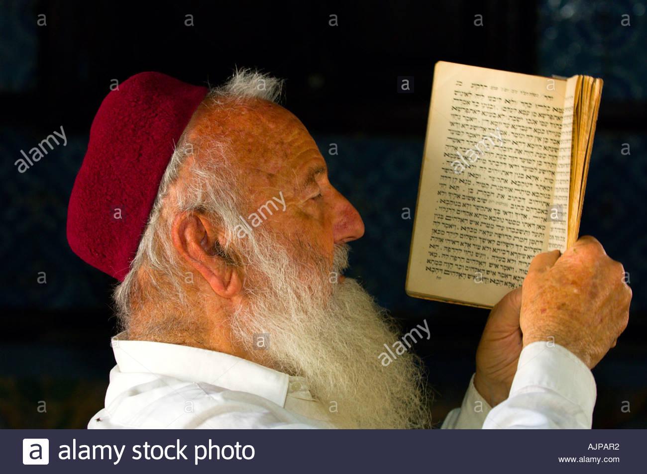 Rabbi reading siddur (prayer book), El Ghriba Synagogue, Djerba Island, Tunisia - Stock Image