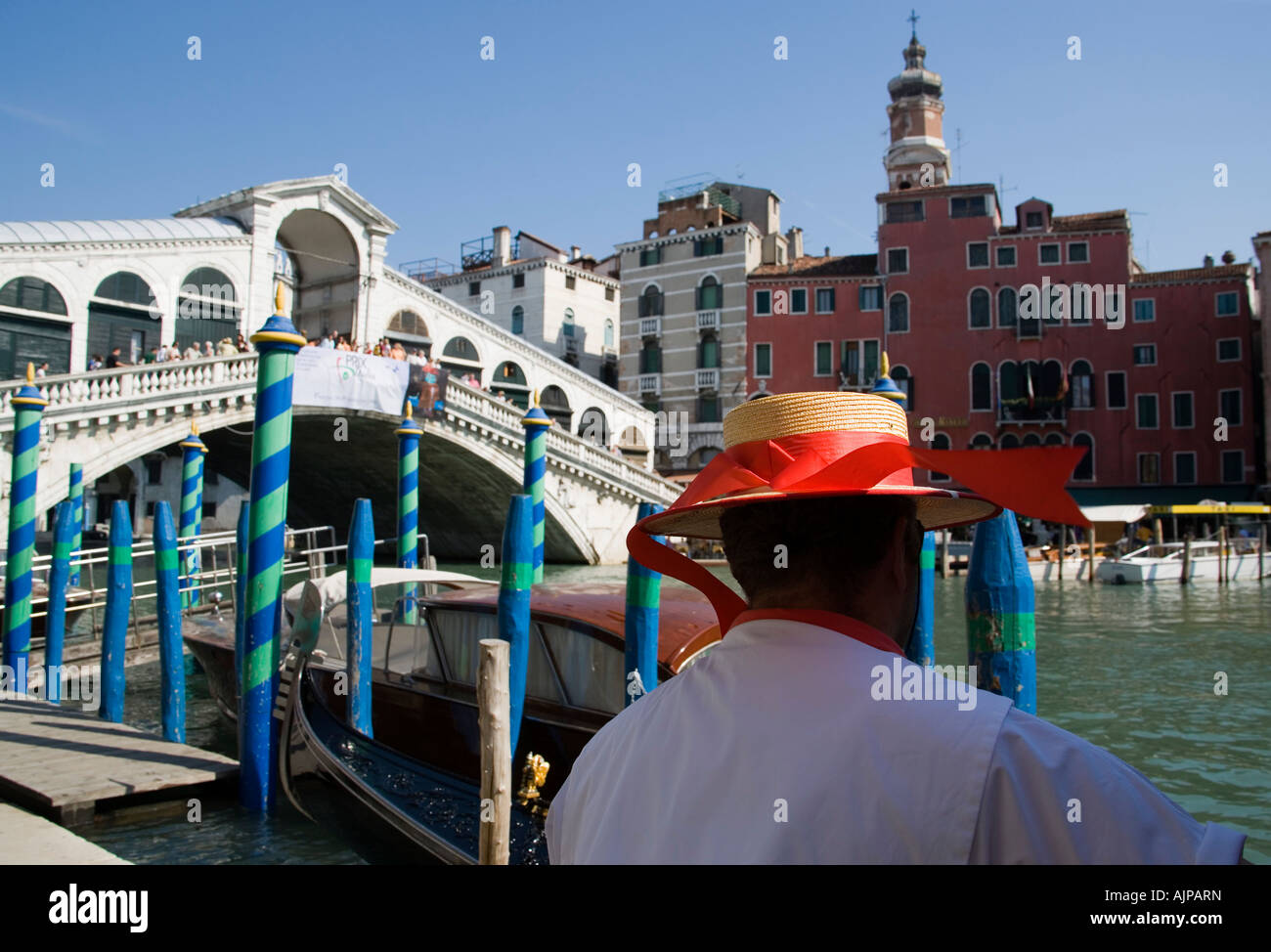 Italy Veneto Venice Gondolier Wearing A Straw Boater Hat Close To His Gondola Moored Beside The Tourist Crowded - Stock Image