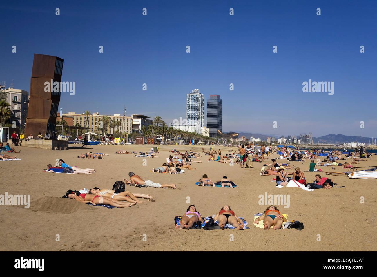 Spain Barcelona beach Platja de la Barceloneta people Sculpture by Rebecca Horn girls sunbathing - Stock Image