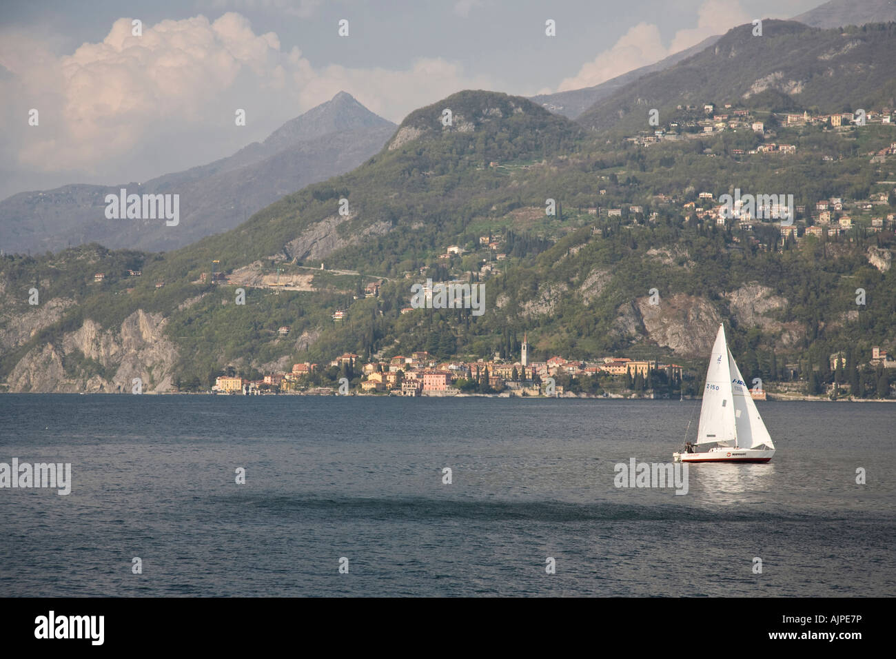 Yacht sails between Varenna and Bellagio on Lake Como, Italy - Stock Image