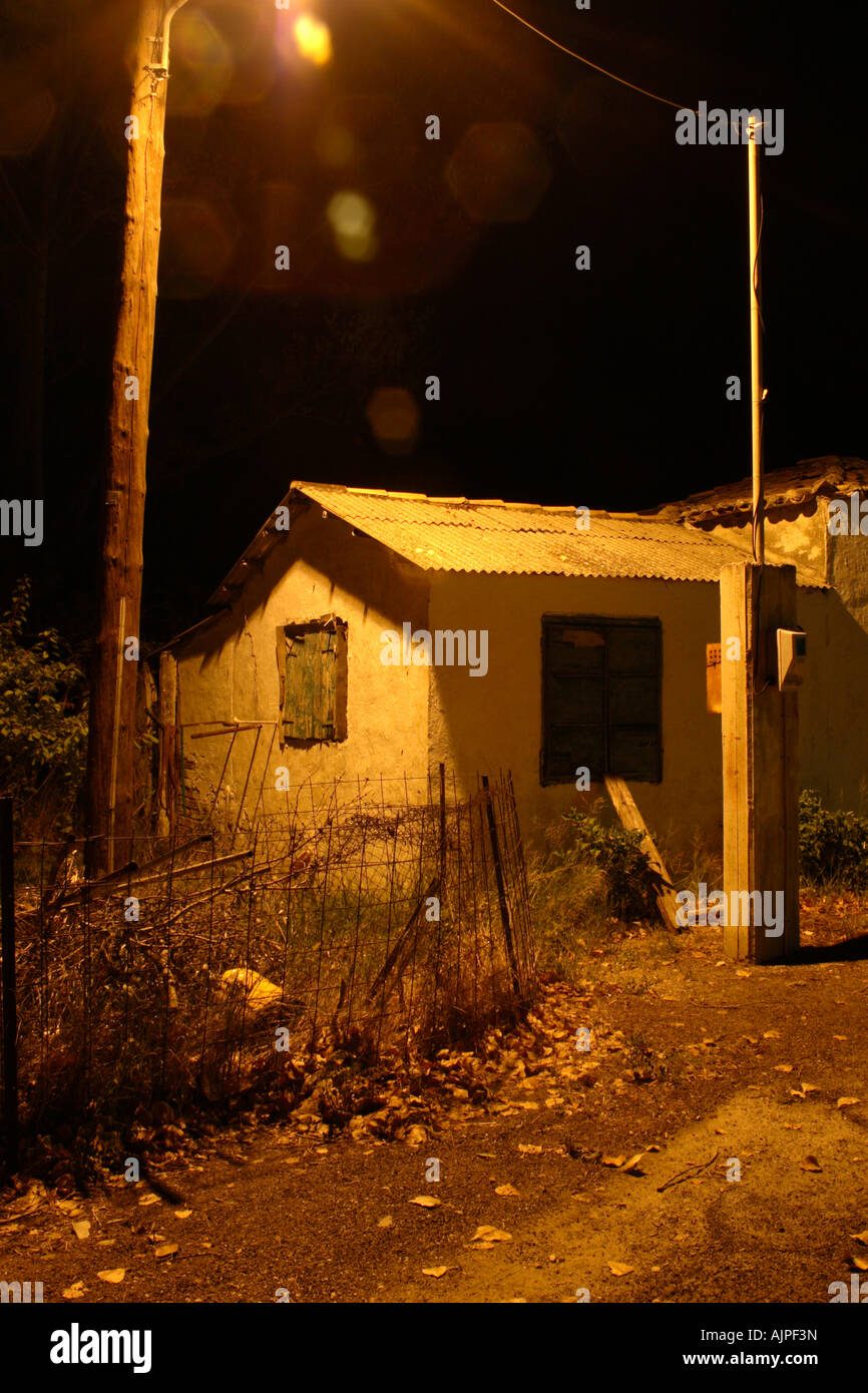 A creepy old building lit at night by overhead orange light. - Stock Image