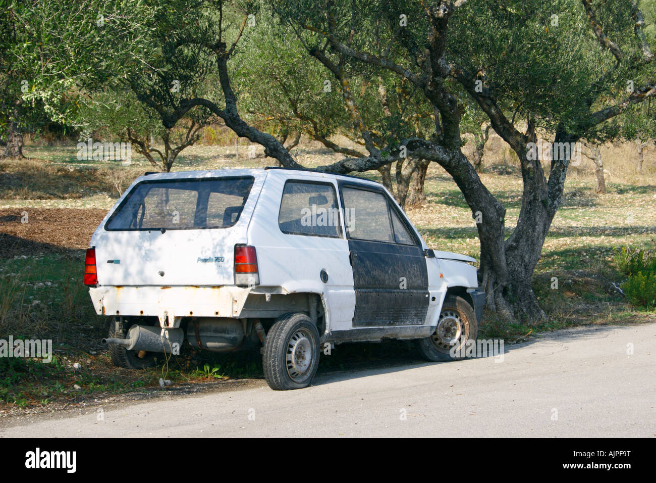 An abandon car next to an Olive trees, Zakynthos, Greece. - Stock Image