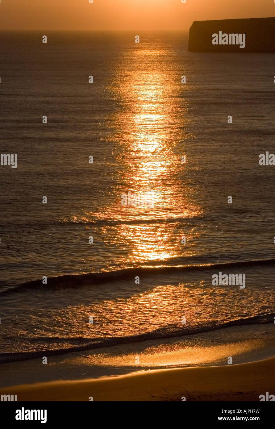 Setting sun glinting off waves lapping onto the shoreline between Cabo de Sao Vincente and Ponta de Sagres Algarve - Stock Image