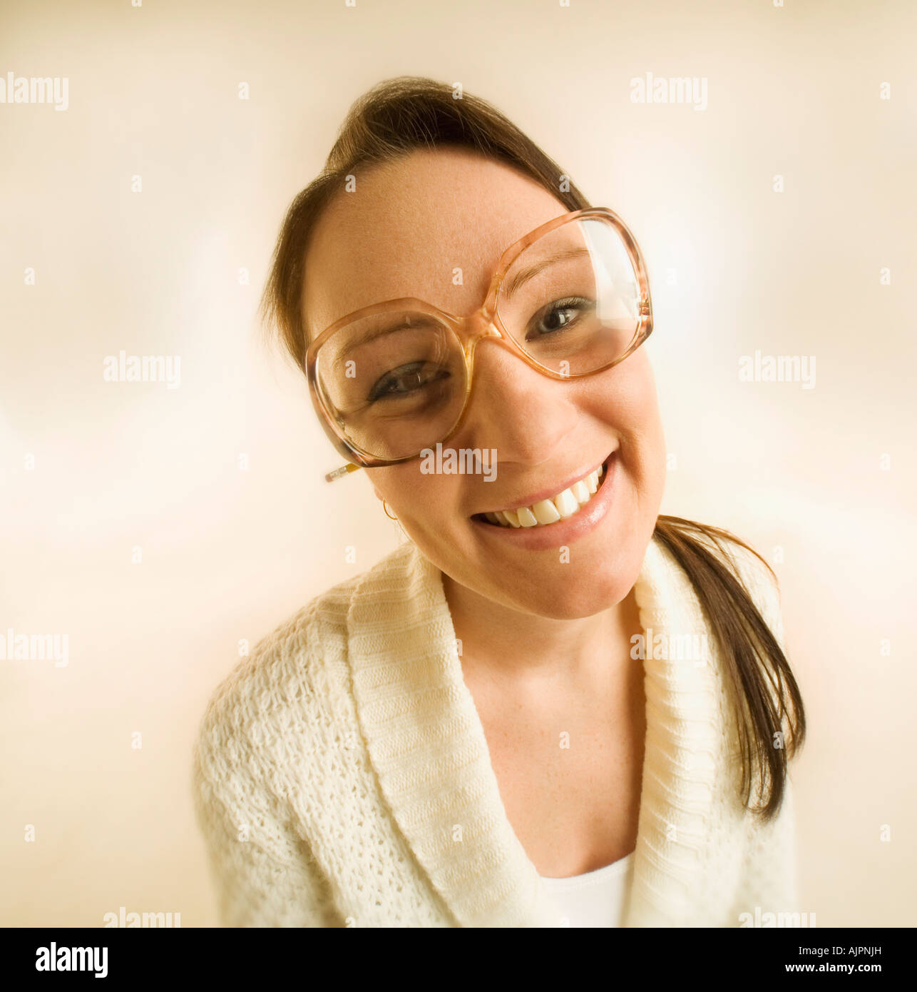 Young woman smiling and wearing eyeglasses - Stock Image