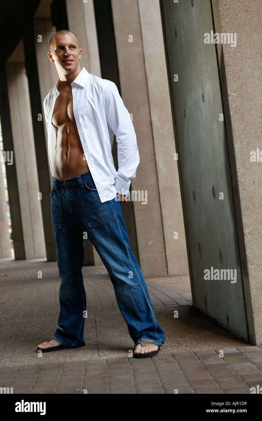 Fit Male Model Posing In White Open Shirt And Jeans Stock Photo