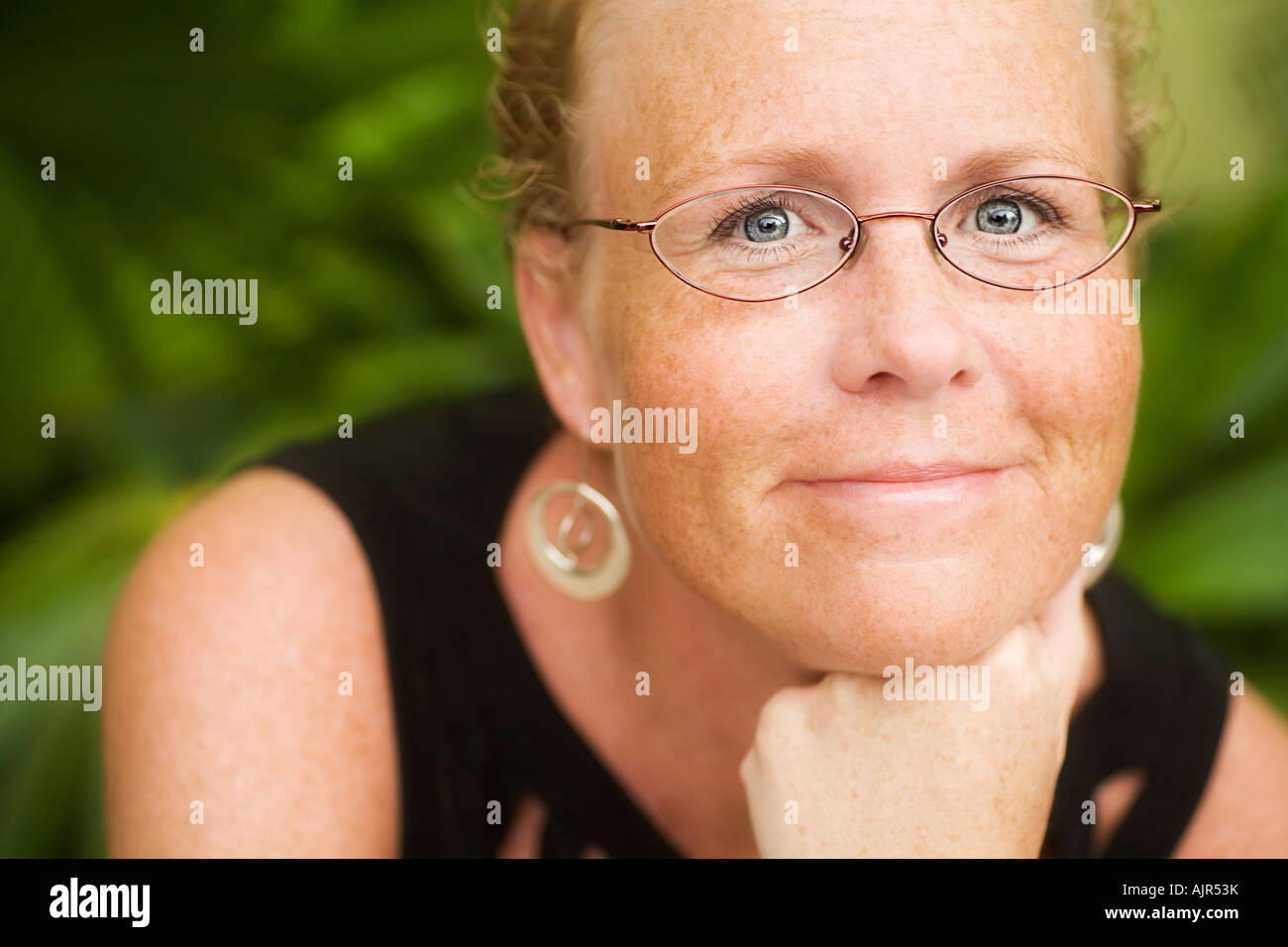 Mid adult woman smiling and posing for picture - Stock Image