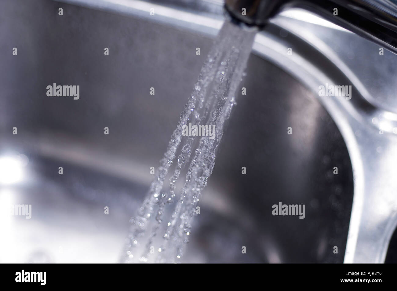 Water pouring from a kitchen tap - Stock Image