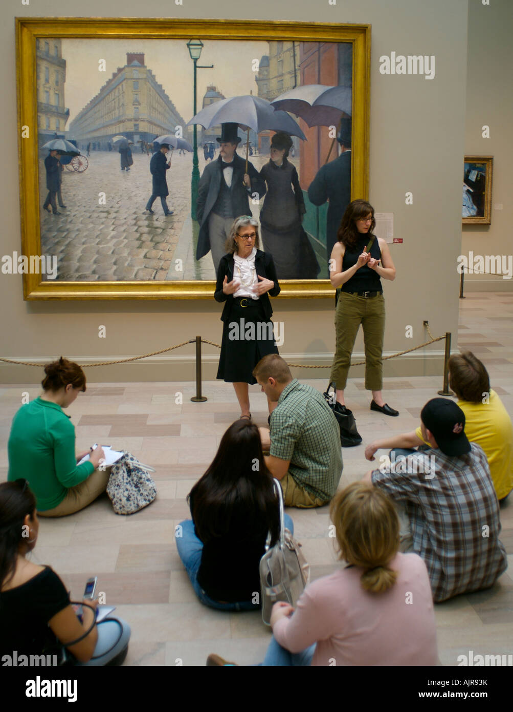 Museum tour guide and her sign language translator lecture a group of students - Stock Image