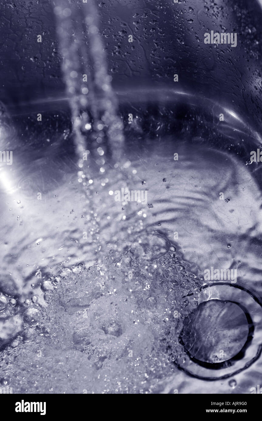 Water pouring down the sink from a tap - Stock Image