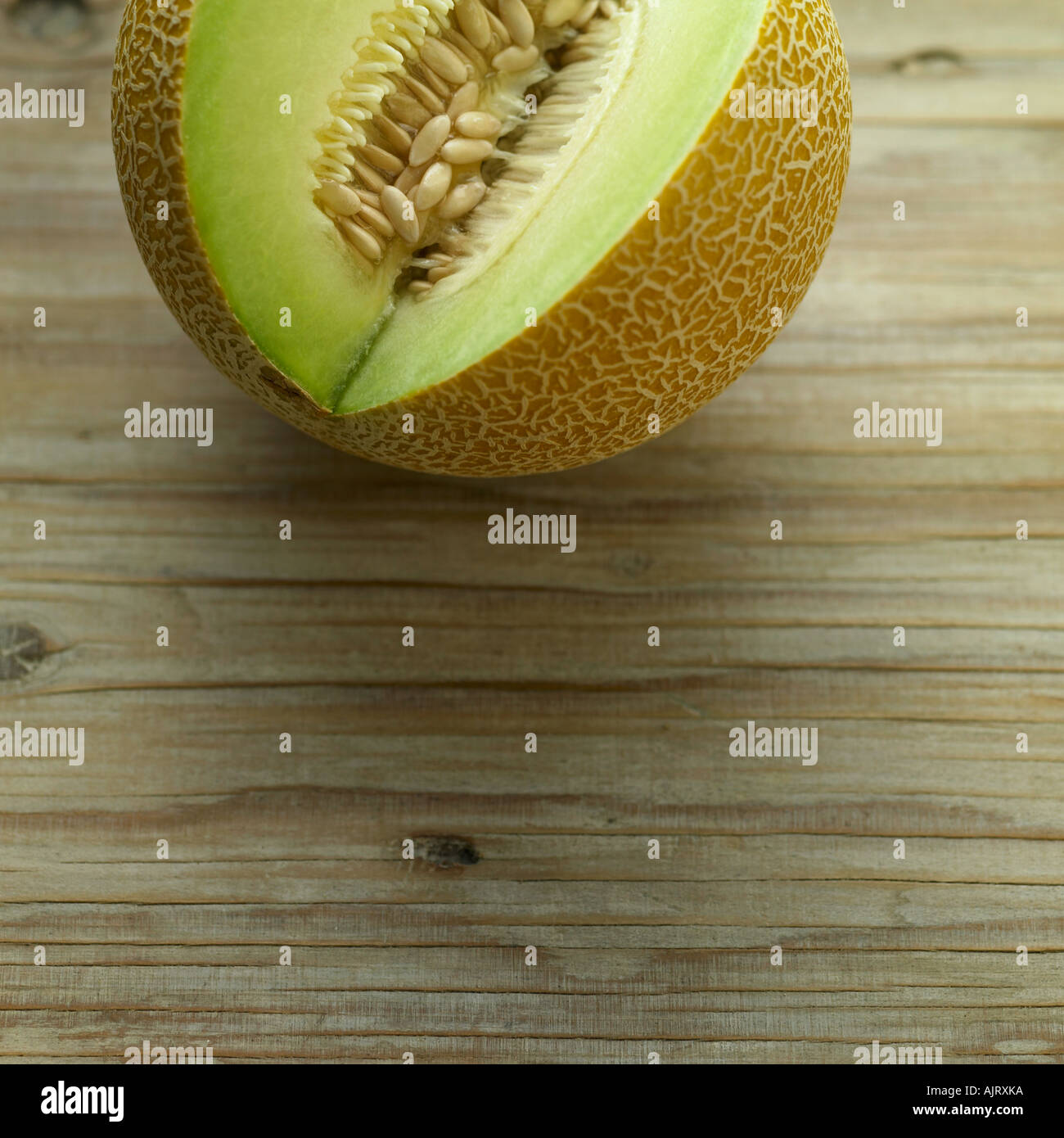 Galia melon on pale wooden background - Stock Image
