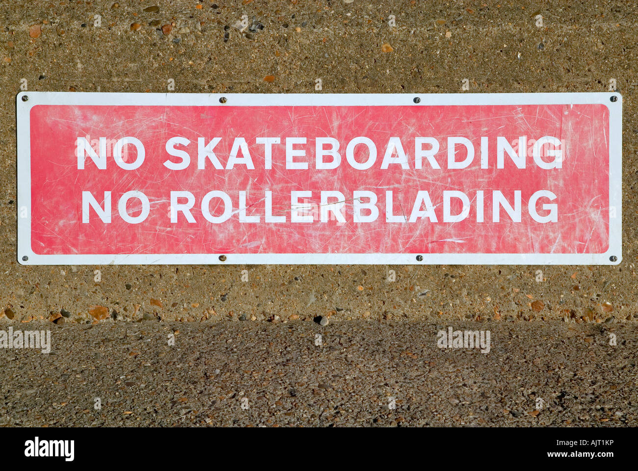 No Skateboarding sign covered in marks from skateboards and rollerblades - Stock Image