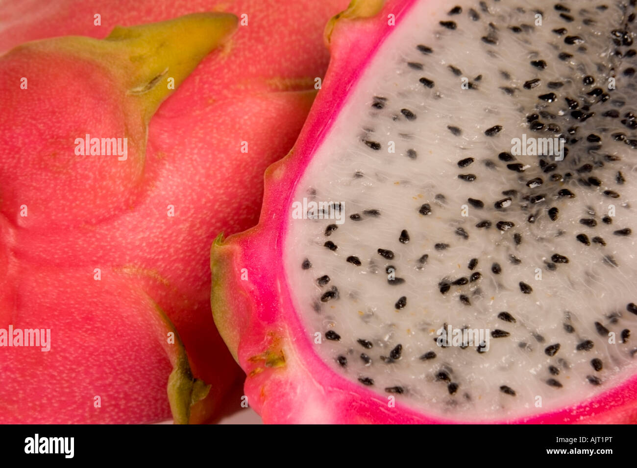 Ripe dragon fruit, hylocereus undatus, cut in half to show the white flesh and seeds - Stock Image