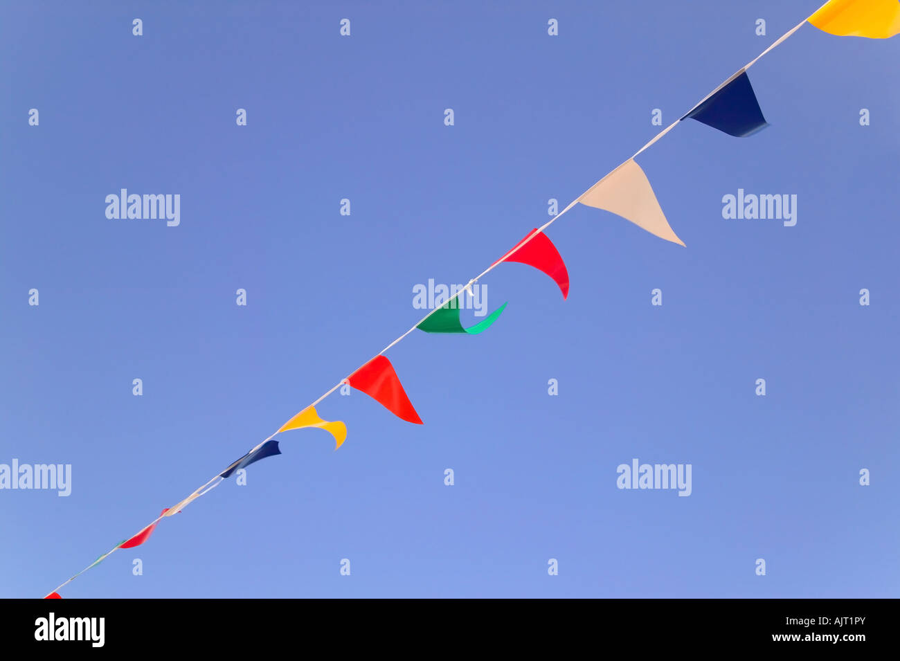 Colorful bunting flags against a blue sky - Stock Image
