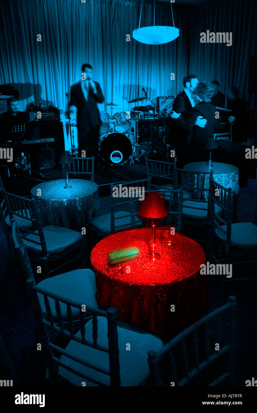 Nightclub scene, tables & chairs, blue room with table highlighted in red light.  Singer and a single couple - Stock Image