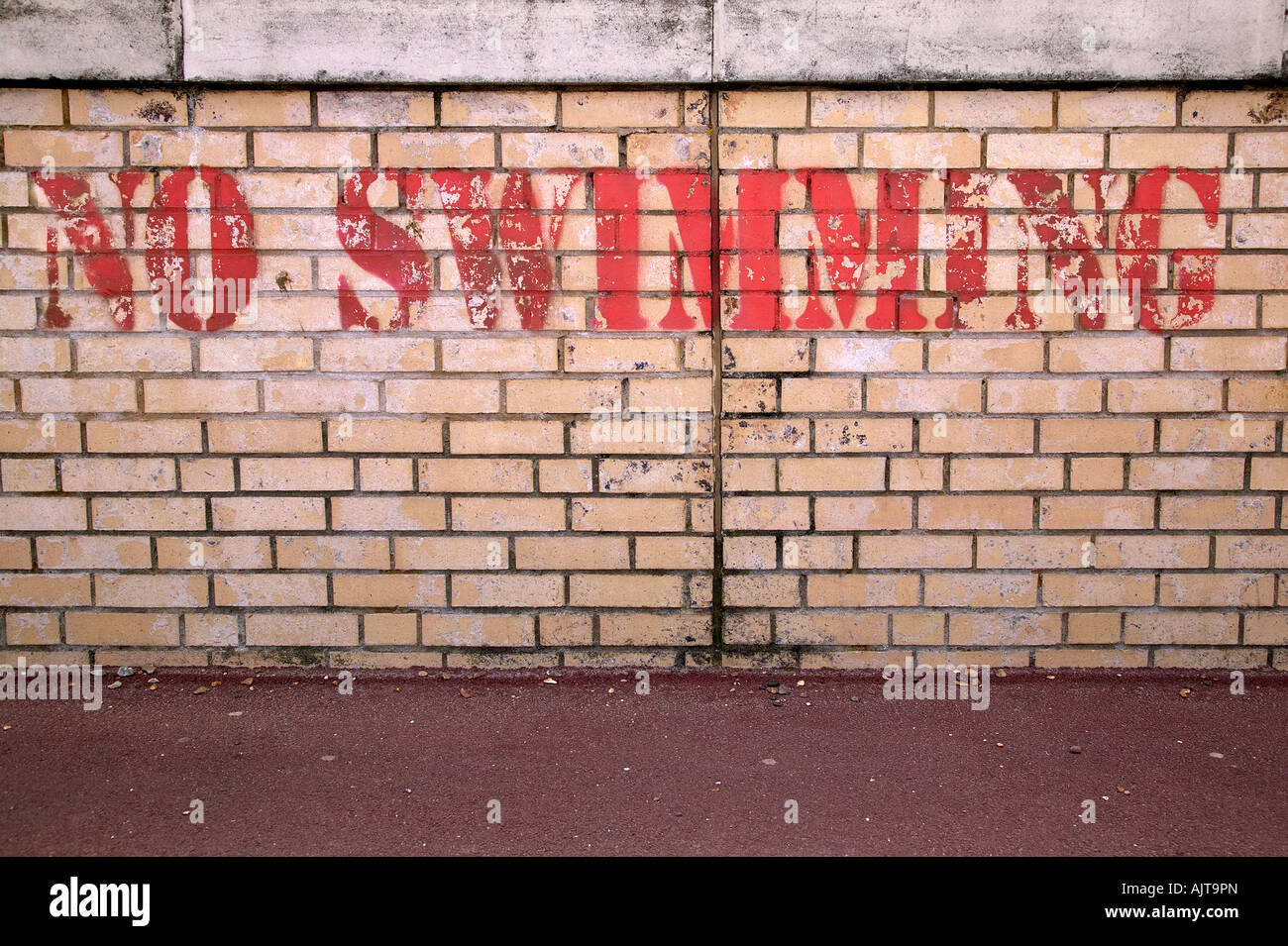 No Swimming stencilled on a brick wall - Stock Image