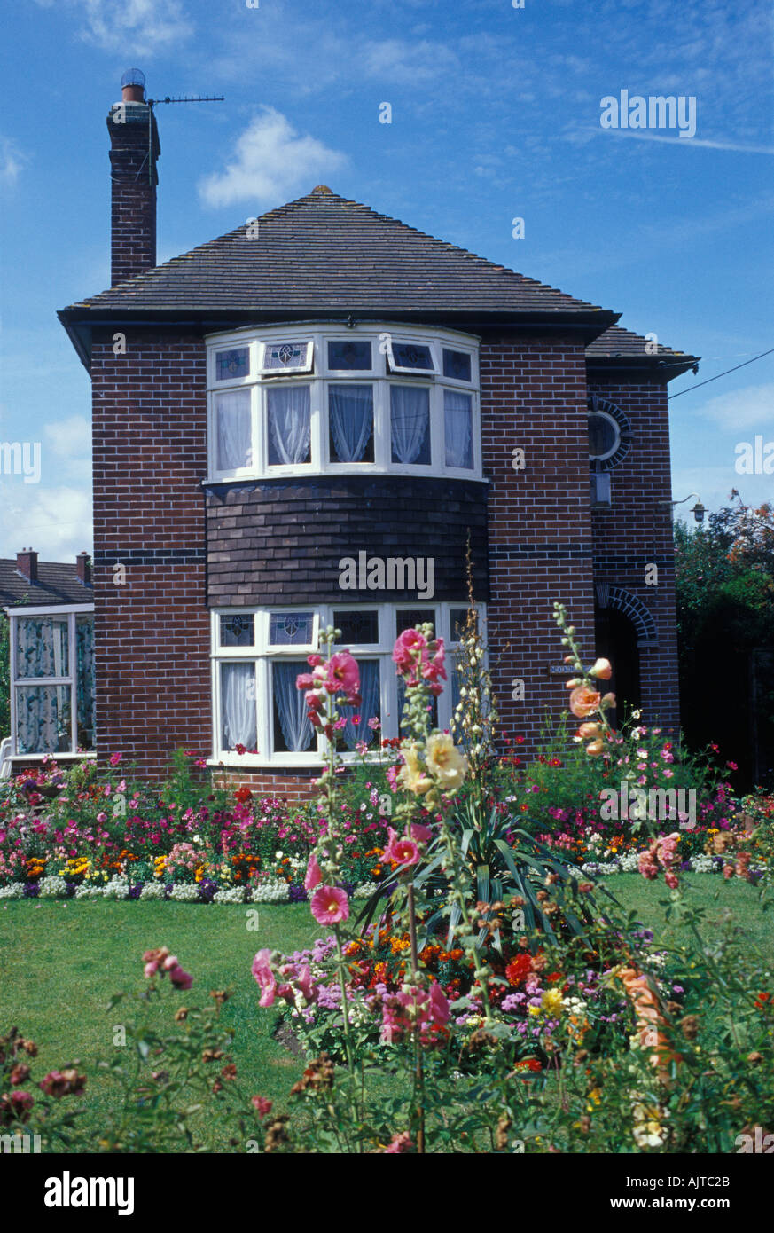 Evercreech Somerset England 1920s 30s detached house of brick with summer front garden flowers lawn west country Stock Photo