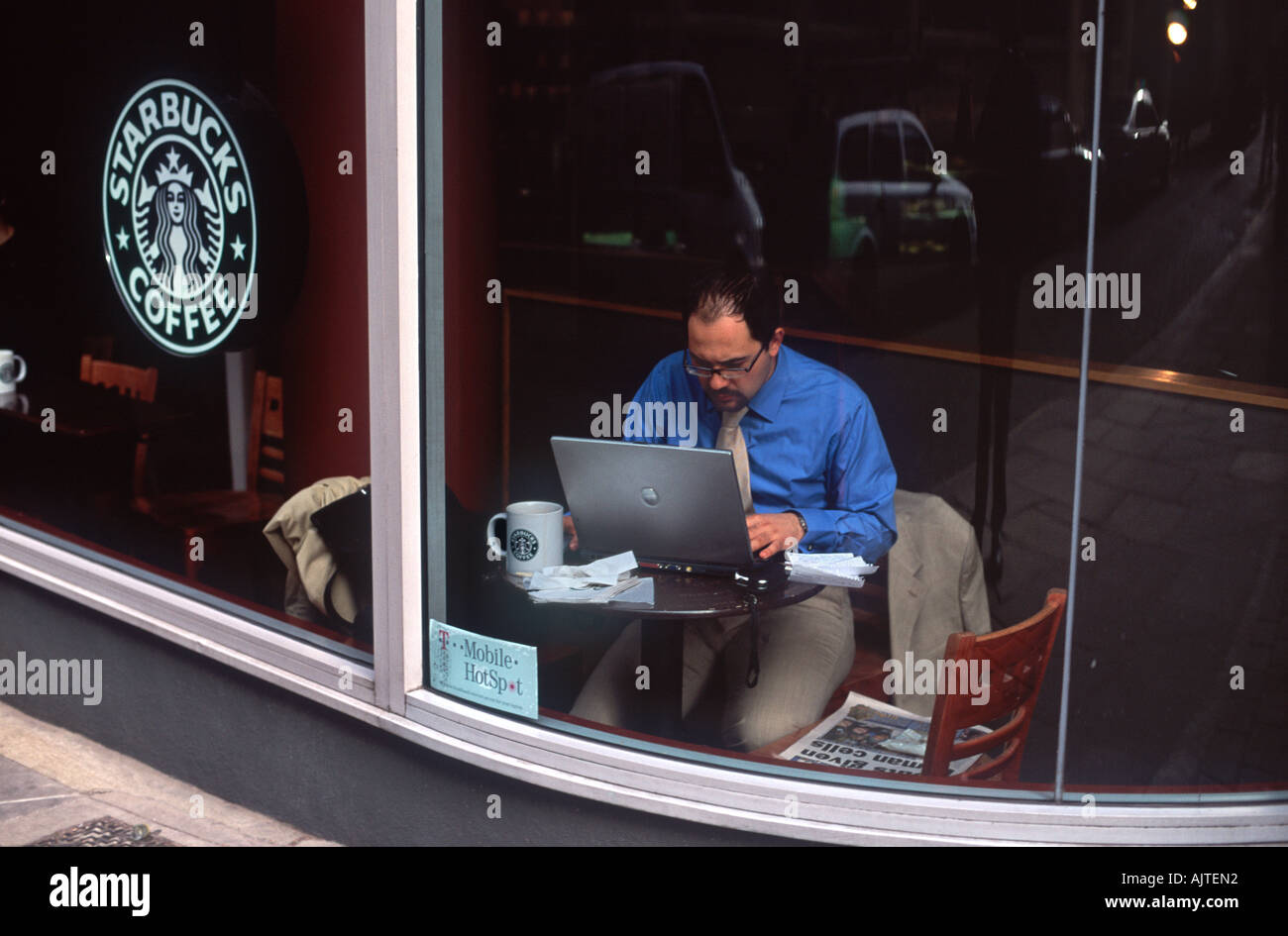 Wireless mobile worker: Man intently working at a laptop computer in the window of a coffee shop, City of London, England - Stock Image