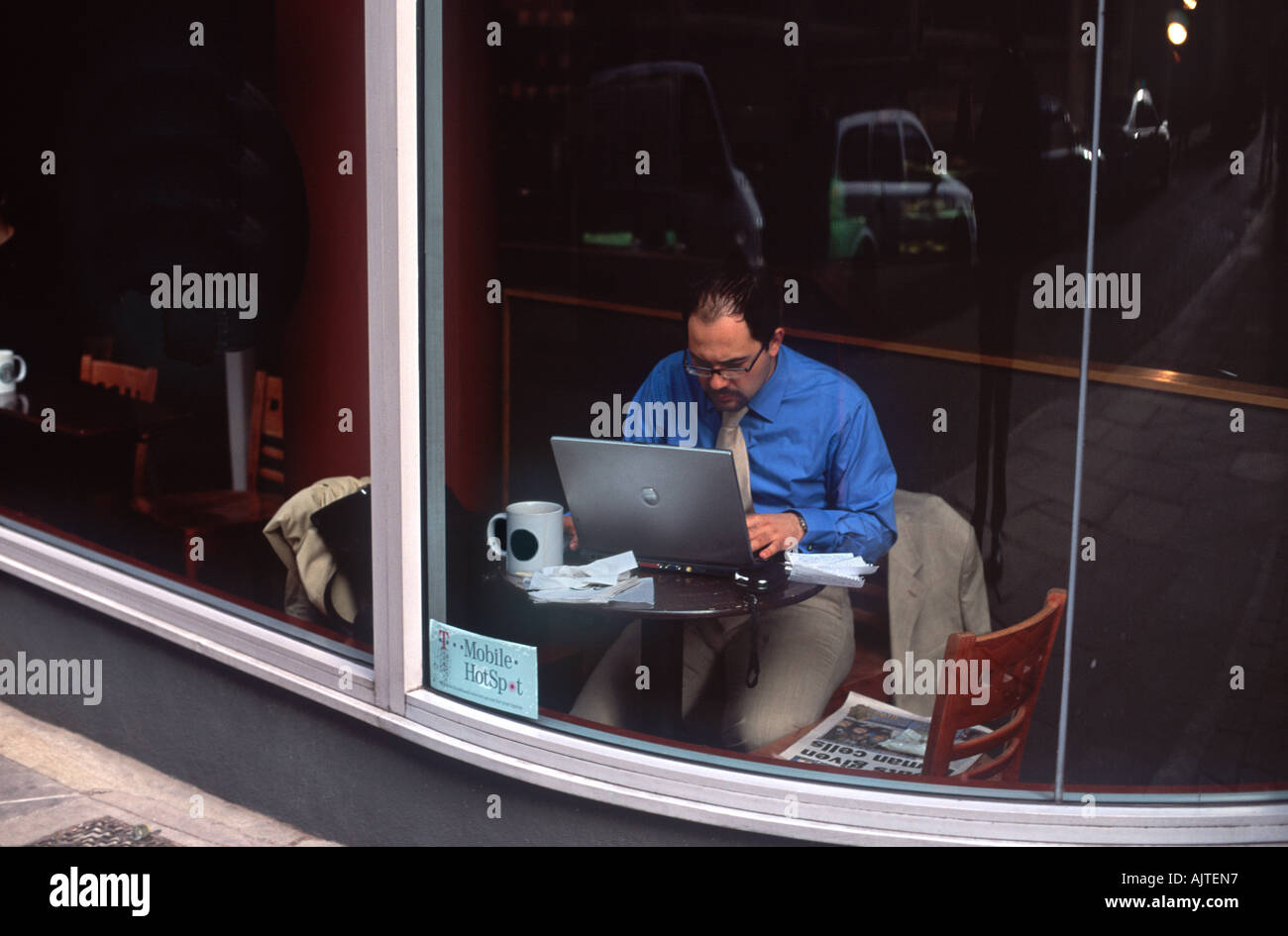No-logo-version: Wireless mobile worker keying intently at a laptop computer in the window of a coffee shop, City of London - Stock Image