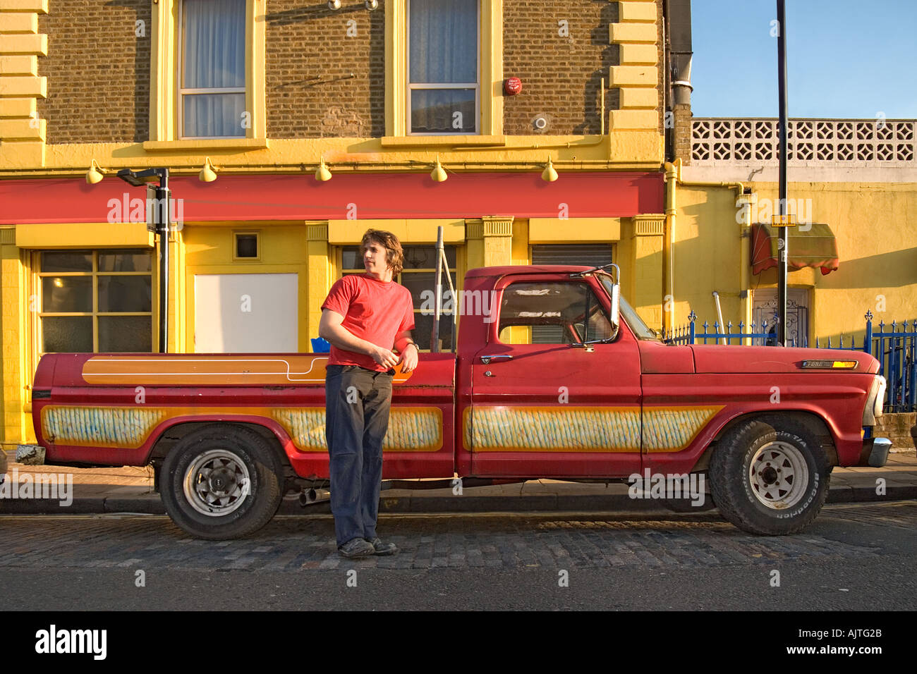 Ford F100 Pickup Truck Stock Photos 1954 Pick Man Standing By Red With A Bright And Yellow Building In
